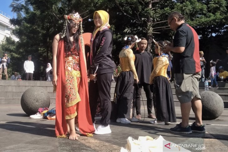 Residents take pictures with Sintren dancers in Cikapayang Park, Bandung, on Sunday (04/21/2019)